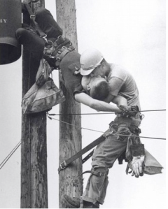 Photograph of one utility worker saving the life of another.